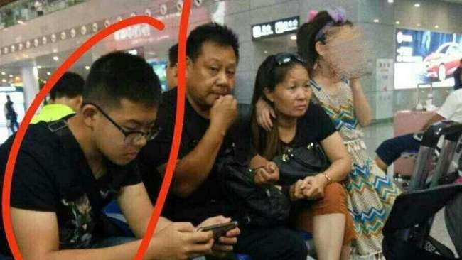 Screen shot of Duan (1st left) sitting with his family at the Nanjing South Railway Station [File photo: Weibo.com]