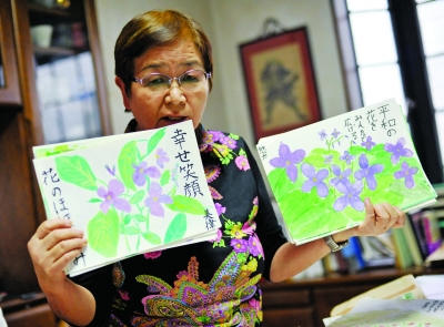 Ookado Takako shows pictures of peace symbolizing orychophragmus drawn by her students. [Photo: ifeng.com]