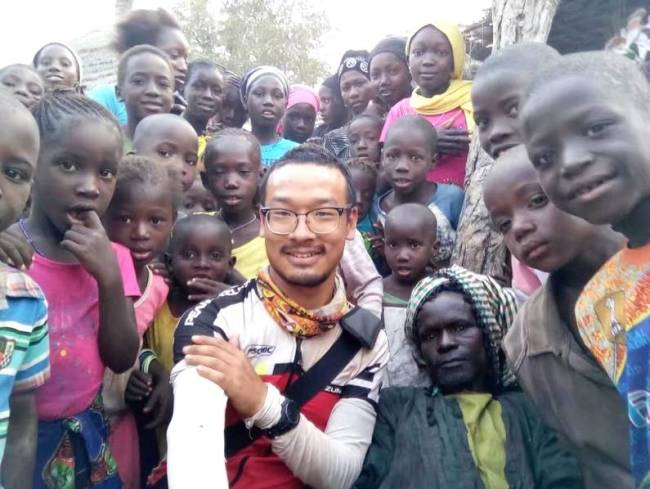 Yuan Jianglei poses for a photo with his African friends. [Photo: Beijing Youth Daily]