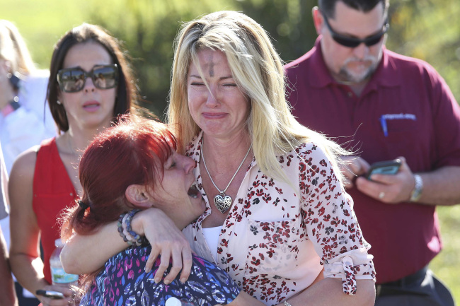 Parents wait for news after a reports of a shooting at Marjory Stoneman Douglas High School in Parkland, Fla., on Wednesday, Feb. 14, 2018. [Photo: AP Photo/Joel Auerbach]