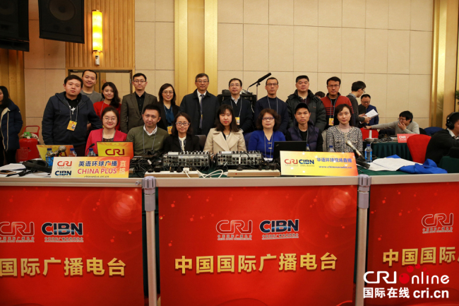 Live broadcast team members of China Radio International pose for a photo ahead of a news conference held by Chinese Foreign Minister Wang Yi in Beijing, on March 8, 2018. [Photo: China Plus]