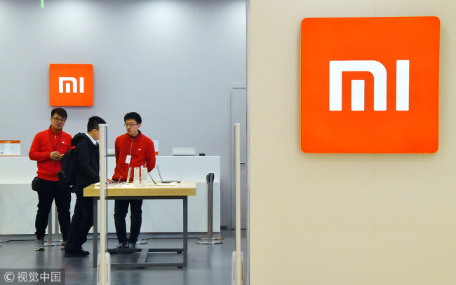 Staff introduce Xiaomi products to customer at a Xiaomi store in Beijing, March 9, 2018. [Photo: VCG]