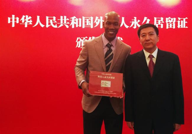 """Former NBA star Stephon Marbury (L) poses with Zhang Jiandong, deputy Mayor of Beijing, during a ceremony in Beijing, capital of China, April 18, 2016. Stephon Marbury, a leading player in Beijing Duck basketball team who helped the team winning three champions in the Chinese basketball league, received his Chinese """"green card"""", or People's Republic of China Foreigner's permanent residence card in Beijing on April 18, 2016. [File Photo: Xinhua]"""