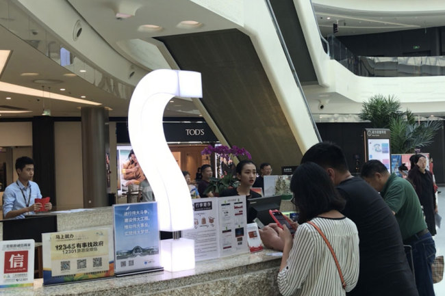 A photo shows visitors at the information desk of the China Duty Free Mall in Sanya, Hainan province, March 27, 2018. [Photo: China Plus/Ge Anna]