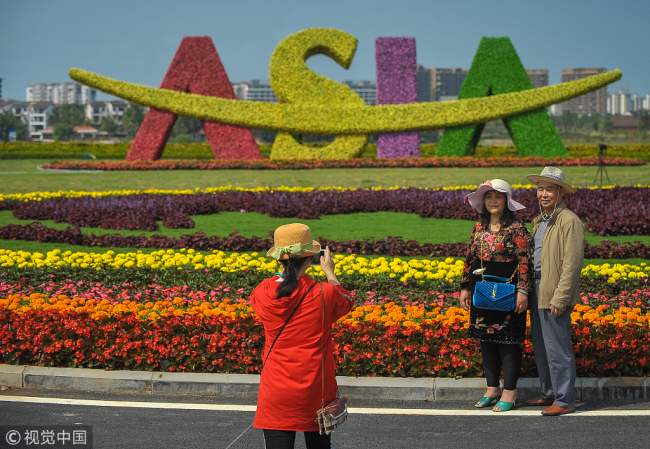 Visitors pose for photos in front of a plant statue of Boao Forum for Asia logo in Boao, Hainan Province, on March 23, 2018. [File photo: VCG]