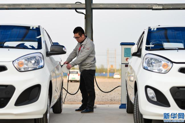 A man charges an electric car in Qinghe County, Hebei Province. [File Photo: Xinhua]