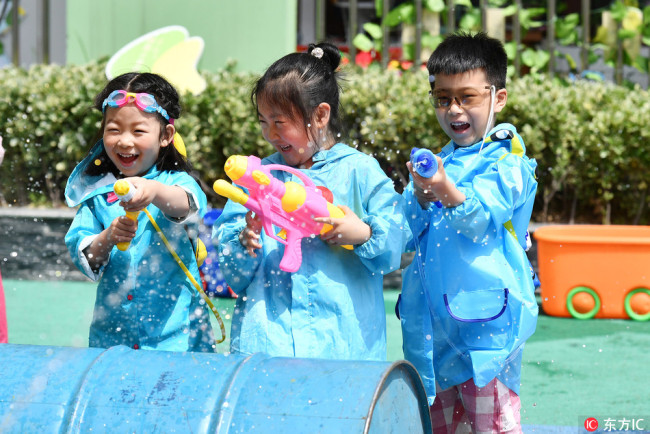 Kindergarten kids play with water pistols during celebrations for the upcoming Children's Day in Huai'an, Jiangsu Province, Wednesday, May 30, 2018. [Photo: VCG]