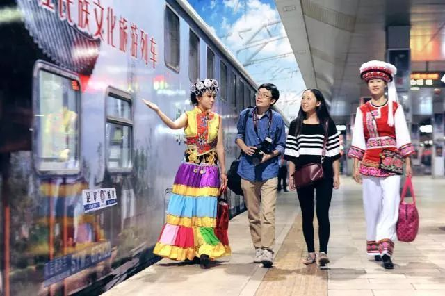 Crew members wearing ethnic outfits welcome passengers outside a tourist train linking Kunming and Lijiang in Yunnan Province. [Photo: China Railway]