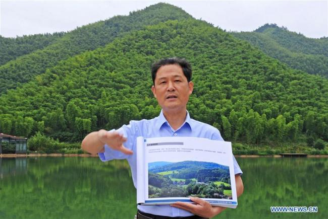 Pan Wenge, secretary of the Communist Party of China local branch in the Yucun Village, shows the plans to upgrade the village to a 5A tourist destination, in Yucun Village of Anji County, east China's Zhejiang Province, June 2, 2018. In 2017, there were an estimated 400,000 visitors from home and abroad to Yucun. [Photo:Xinhua/Tan Jin]