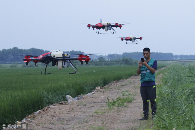 A Chinese technician controls three XAG drones at the same time. [File Photo: VCG]