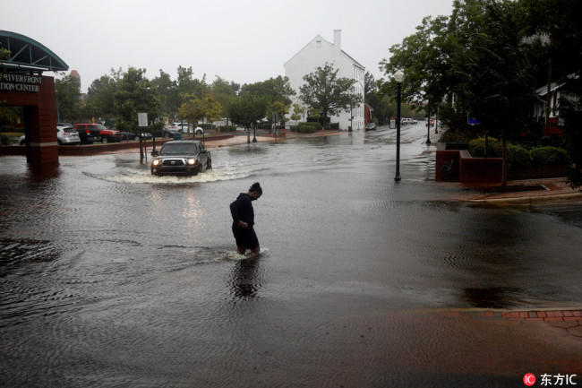 A man tries to cross the street during the heavy rain of outer bands of Hurricane Florence in New Bern, North Carolina, United States on September 13, 2018.[Photo: IC]