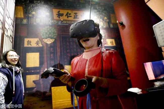 A visitor has an immersive experience using a VR headset during a digital exhibition at the Palace Museum in Beijing on October 10, 2017. [Photo: VCG]