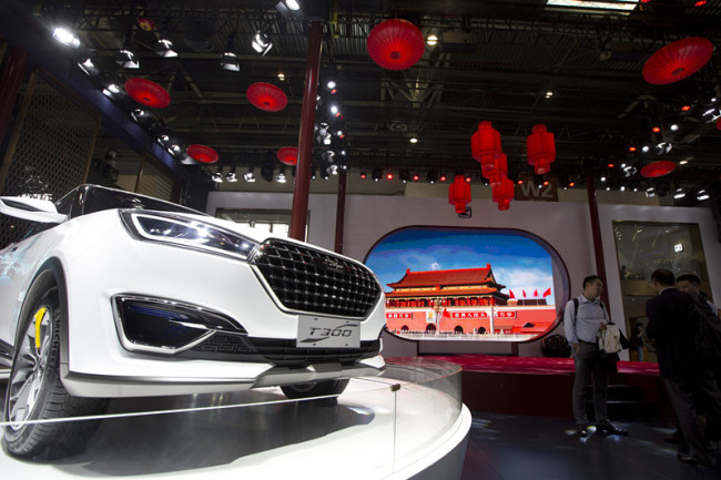 In this file photo taken Monday, April 25, 2016, visitors to Auto China 2016 stand near Zotye Auto's T300 SUV displayed in Beijing, China. [Photo: AP/Ng Han Guan]