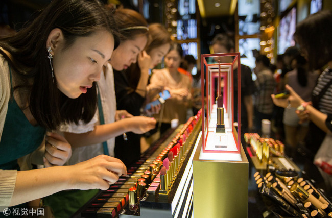 In this November 29, 2016 file photo, customers choose cosmetic products at a duty-free store in Sanya, south China's Hainan Province. [Photo: VCG]