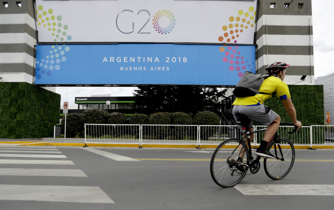 A man rides a bicycle past a banner promoting the G20 summit at the Costa Salguero Center, in Buenos Aires, Argentina, Tuesday, Nov. 27, 2018. [Photo: IC]