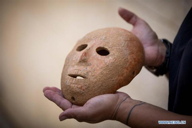 Made of pinkish-yellow limestone, the mask was carefully shaped into a human face, with four holes drilled along the perimeter. [Photo: Xinhua]