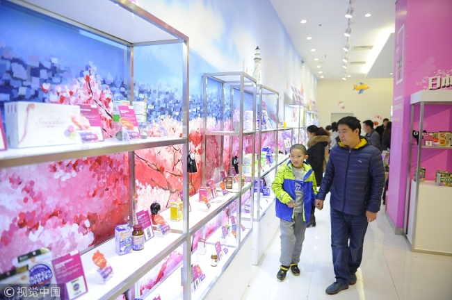 Consumers select goods at a cross-border e-commerce offline store in Tianjin. [File photo: VCG]