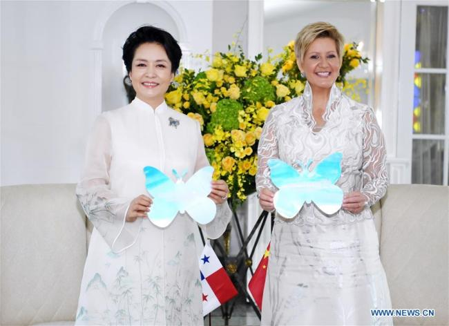 Peng Liyuan (L), wife of Chinese President Xi Jinping, and World Health Organization goodwill ambassador for tuberculosis and HIV/AIDS and UNESCO special envoy for the advancement of girls' and women's education, and Panamanian First Lady Lorena Castillo Garcia, special ambassador for UNAIDS in Latin America, pose for photos holding colorful paper butterflies, which symbolize the Zero Discrimination campaign, to show their solid support for the global cause against AIDS in Panama City, Panama, Dec. 3, 2018. [Photo: Xinhua/Yan Yan]
