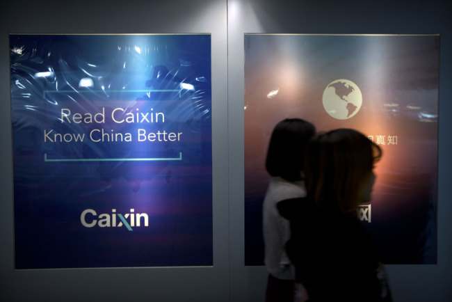 "In this Jan. 18, 2018 photo, staffers walk past a billboard reading ""Read Caixin - Know China Better"" at the Caixin Media offices in Beijing. [Photo: AP]"