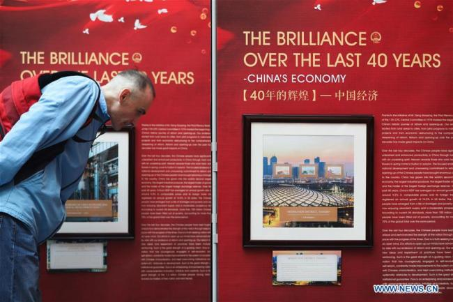 """A visitor watches the stamps showing China's economic achievements during the """"China-Great Change"""" stamp exhibition in Leuven, Belgium, Dec. 11, 2018. A large-scale stamp exhibition was opened Tuesday at Belgium's University of Leuven to commemorate the 40th anniversary of China's reform and opening up. Themed """"China - Great Change"""", the exhibition, showcasing 188 stamps, aims to offer a glimpse into the significant changes that have transpired in China over the last four decades.[Photo:Xinhua]"""