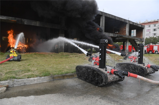 Firefighting robots spray water during a drill at a factory in Ningde, Fujian Province on Wednesday, December 12, 2018. [Photo: Xinhua]