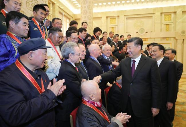 Chinese President Xi Jinping, also general secretary of the Communist Party of China (CPC) Central Committee and chairman of the Central Military Commission, and other Chinese leaders shake hands with the award recipients and their relatives after a grand gathering to celebrate the 40th anniversary of China's reform and opening-up at the Great Hall of the People in Beijing, capital of China, Dec. 18, 2018. Award recipients were presented medals for their outstanding contributions to the reform and opening-up. Xi made an important speech at the gathering. [Photo: Xinhua/Ju Peng]