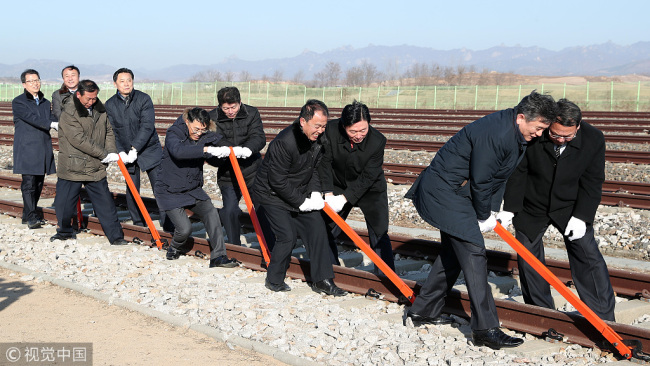 South and North Korea's officials try to connect the railroad during the ceremony for a project to modernize and connect roads and railways over the border between the Koreas at Panmun Station on December 26, 2018 in Kaesong, North Korea. [Photo: Korea Pool/Getty Images]