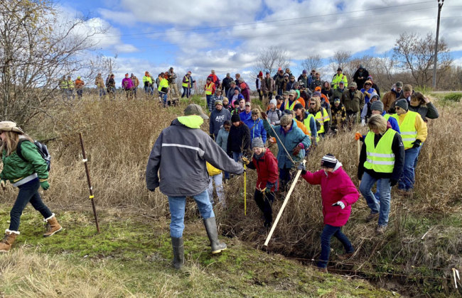 In this Oct. 23, 2018, file photo, volunteers cross a creek and barbed wire near Barron, Wis., on their way to a ground search for 13-year-old Jayme Closs who was discovered missing Oct. 15 after her parents were found fatally shot at their home. The Barron County Sheriff's Department said on its Facebook page that that the teenager Closs has been located Thursday, Jan. 10, 2019, and that a suspect was taken into custody. [File Photo: AP/Jeff Baenen]
