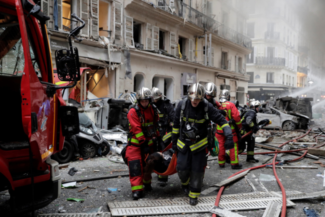 Firefighters evacuate an injured person after the explosion of a bakery on the corner of the streets Saint-Cecile and Rue de Trevise in central Paris on January 12, 2019. [Photo: AFP/Thomas Samson]