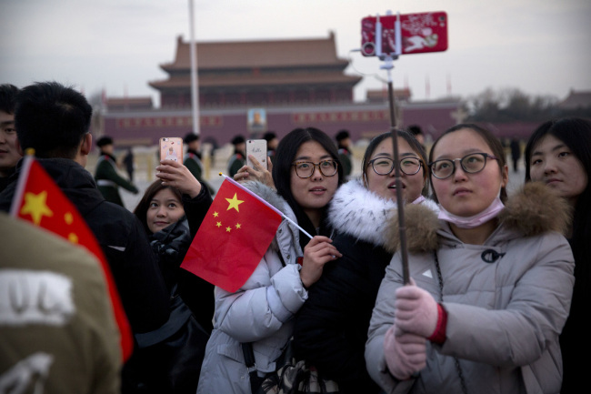 Tourists pose for selfies on Tiananmen Square in Beijing, Monday, March 5, 2018. [Photo: AP Photo/Mark Schiefelbein]