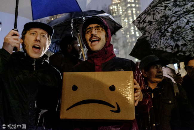 A demonstrator holds a cardboard box featuring an altered version of the Amazon.com Inc. logo during a protest against the planned Amazon office hub in the Long Island City of New York, U.S, on Monday, Nov. 26, 2018. [File Photo: VCG]