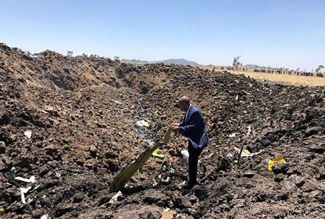 This handout photograph released from the Twitter account of Ethiopian Airlines on March 10, 2019, shows a man inspecting what is believed to be wreckage at the crash site of an Ethiopia Airlines aircraft near Bishoftu, a town some 60 kilometres southeast of Addis Ababa, Ethiopia. [Photo: AFP]