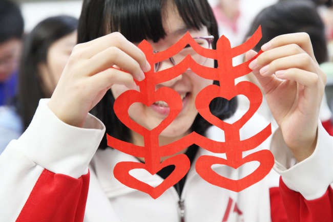 "A student displays her paper-cutting of the traditional Chinese ornament design ""Double Happiness"" during an elective class on paper-cutting at the High School Affiliated to Renmin University of China in Beijing on Thursday, March 7, 2019. [Photo: China Plus]"