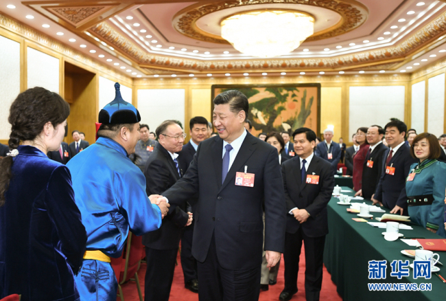 President Xi Jinping shakes hands with Wu Yunbo, a legislator from the Inner Mongolia Autonomous Region, at the second session of the 13th National People's Congress in Beijing on March 5, 2019. [Photo: Xinhua]