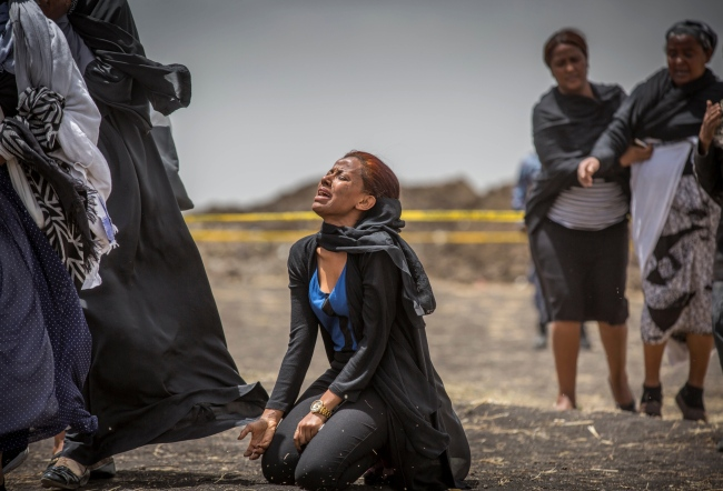 Ethiopian relatives of crash victims mourn and grieve at the scene where the Ethiopian Airlines Boeing 737 Max 8 crashed shortly after takeoff on Sunday killing all 157 on board, near Bishoftu, south-east of Addis Ababa, in Ethiopia Thursday, March 14, 2019. The French air accident investigation authority said Thursday that it will handle the analysis of the black boxes retrieved from the crash site and they have already arrived in France but gave no time frame on how long the analysis could take. [Photo via AP/Mulugeta Ayene]