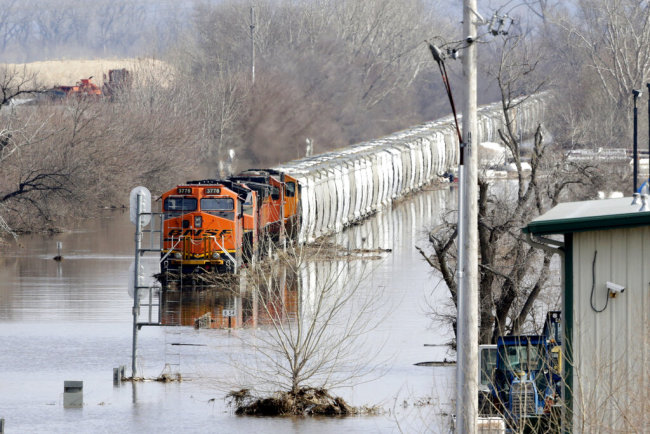 A BNSF train sits in flood waters from the Platte River, in Plattsmouth, Neb., Sunday, March 17, 2019. Hundreds of people remained out of their homes in Nebraska, but rivers there were starting to recede. The National Weather Service said the Elkhorn River remained at major flood stage but was dropping. [Photo: AP]