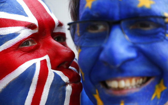 Activists poses with their faces painted in the EU and Union Flag colors during an anti-Brexit campaign stunt outside EU headquarters during an EU summit in Brussels, Thursday, March 21, 2019. British Prime Minister Theresa May is trying to persuade European Union leaders to delay Brexit by up to three months, just eight days before Britain is scheduled to leave the bloc. [Photo: AP]