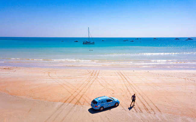"This handout photo taken on July 20, 2018 and released on April 7, 2019 from Dutch driver Wiebe Wakker shows him on Cable Beach in Broome, Western Australia with his retrofitted station wagon nicknamed ""The Blue Bandit"" during his round-the-world trip in the electric car. [Photo: PLUG ME IN PROJECT/Wiebe Wakke/AFP]"