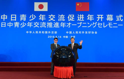 """Chinese State Councilor and Foreign Minister Wang Yi (R) and Japanese Foreign Minister Taro Kono attend the opening ceremony of the """"China-Japan Youth Exchange Promotion Year"""" before the fifth high-level economic dialogue between China and Japan in Beijing, April 14, 2019. [Photo: fmprc.gov.cn]"""
