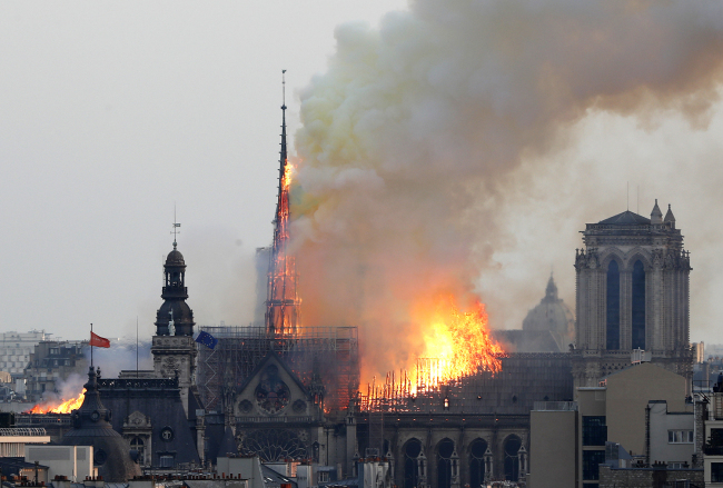 Flames rise from Notre Dame Cathedral as it burns in Paris, Monday, April 15, 2019. [Photo: AP/Thibault Camus]