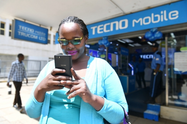 A woman uses her Tecno smartphone outside a Tecno retail store in Kenya's Nairobi, May 9, 2017. Tecno is one of the three major phone brands of Transsion. [Photo: Xinhua]