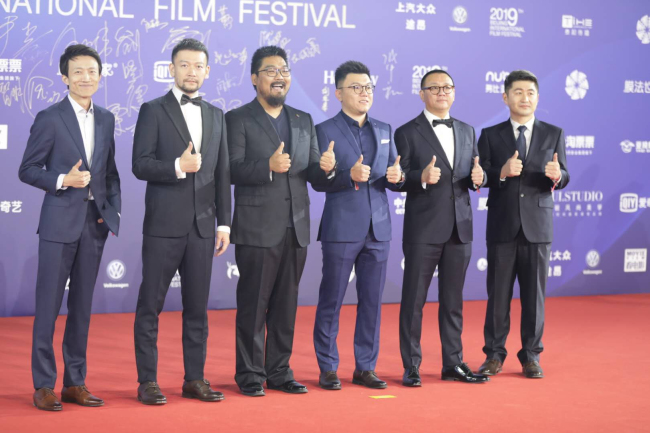 """Director Guo Fan (L2) of """"The Wandering Earth"""" poses on red carpet with crew at the closing ceremony for the 9th Beijing International Film Festival, on April 20, 2019, in Beijing. [Photo: CGTN]"""