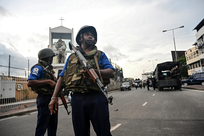 Sri Lankan soldiers stand guard near a car explosion after the police tried to defuse a bomb near St. Anthony's Shrine in Colombo on April 22, 2019, a day after the series of bomb blasts targeting churches and luxury hotels in Sri Lanka. [Photo: AFP/Jewel SAMAD]
