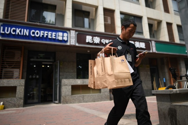 A deliveryman carrying bags of coffee walks out a Luckin Coffee in Beijing on August 2, 2018. [Photo: AFP]