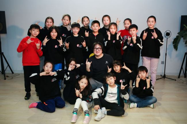 There are about fifty members of Stone and Children Band. Here are some members taking picture with Shi Dongying. [Photo: courtesy of Shi Dongying, music producer of Stone and Children Band]