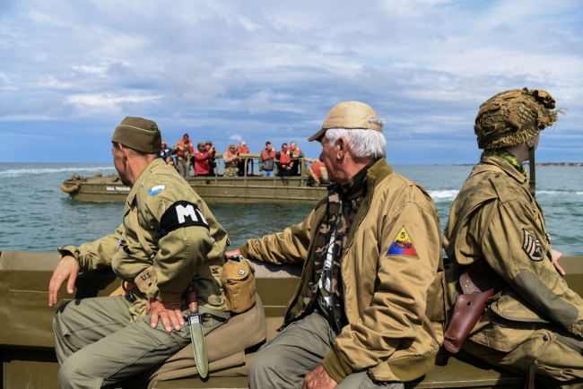 Men dressed as GIs sit on a DUKW (colloquially known as Duck), a six-wheel-drive amphibious modification of the 2 1/2-ton CCKW trucks used by the US military during World War II, on June 4, 2019 off the shores of Arromanches-les-Bains, as part of events for the 75th anniversary of D-Day landings. [Photo: AFP/Alain Jocard]