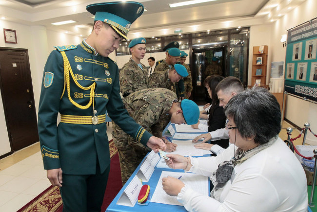 Kazakh servicemen receive ballots at a polling station during Kazakhstan's presidential elections in Nur-Sultan on June 9, 2019. [Photo: AFP/ Stanislav FILIPPOV]