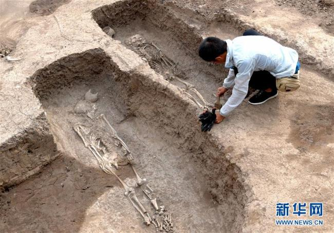 An archaeologist is cleaning a family tomb of ancient bronzeware artisans discovered in central China's Henan Province, June 5, 2019. [Photo: Xinhua]