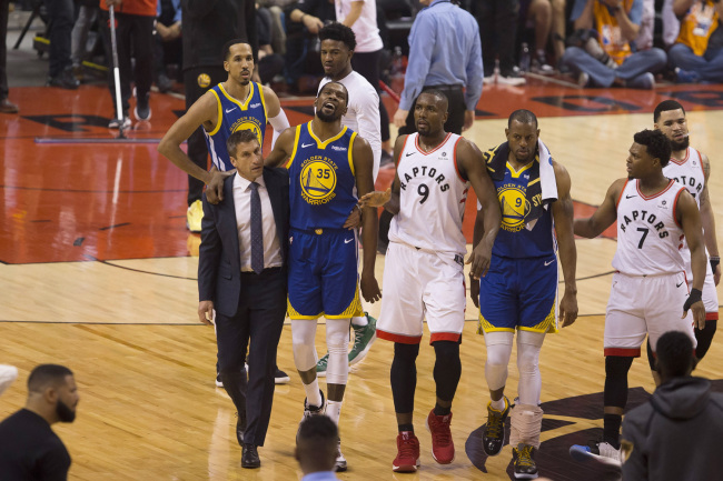 Golden State Warriors forward Kevin Durant (35) walks off the court after sustaining an injury as he is consoled by Toronto Raptors center Serge Ibaka (9) as Warriors forward Andre Iguodala (9) and guard Kyle Lowry (7) look on during first-half basketball action in Game 5 of the NBA Finals in Toronto, Monday, June 10, 2019. [Photo: Chris Young/The Canadian Press via IC]