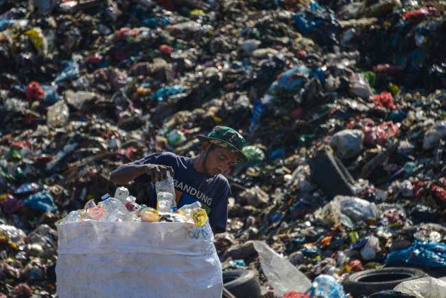 A scavenger collects recyclable plastics at a garbage dump in Banda Aceh, Aceh province on March 23, 2019. [Photo: AFP/CHAIDEER MAHYUDDIN]